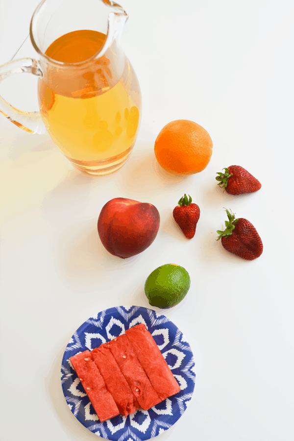 Pitcher of juice next to fresh fruit to make a kids sangria.