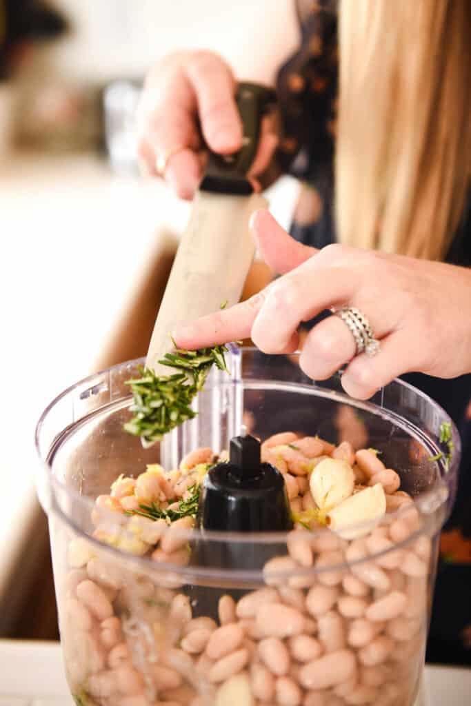 Woman adding chopped garlic to a food processor.